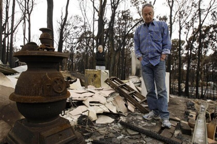 Peter Denson, right, and his daughter Amberley look through the wreckage of Peter's home at Kinglake, north east of Melbourne, Australia Wednesday, Feb. 11, 2009. Residents of towns scorched off the map by Australia's worst-ever wildfires returned to their homes for the first time and found scenes of utter devastation. (AP Photo/Rick Rycroft)