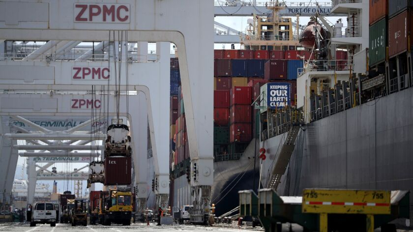 Containers are offloaded from a ship docked at the Port of Oakland in Oakland, Calif., on May 13.