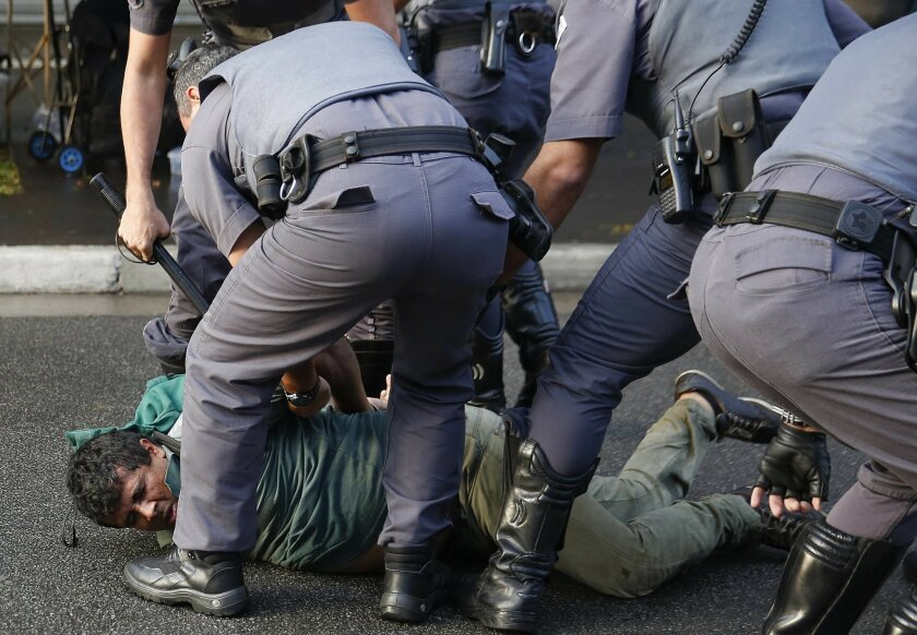 A demonstrator belonging to the Homeless Workers Movement is detained by the police during a protest in Sao Paulo, Brazil, Wednesday, June 1, 2016. The movement organized the protest against acting President Michel Temer and in support of suspended President Dilma Rousseff.  (AP Photo/Andre Penner)