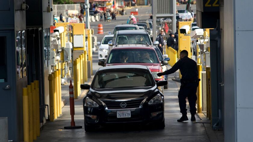 A U.S. Customs and Border Protection officer checks a driver's papers at the San Ysidro Port of Entry border crossing in San Diego on Feb. 10, 2016.