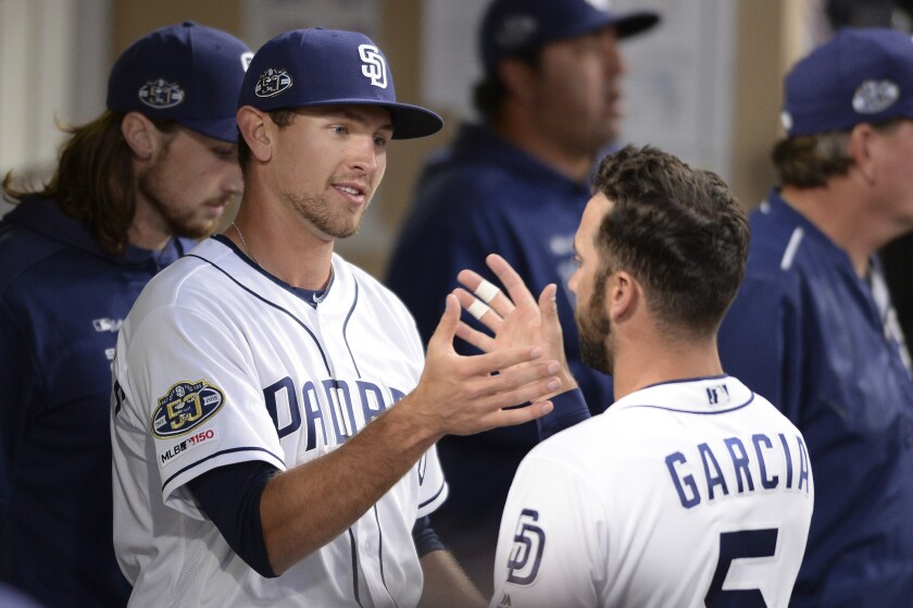 Padres rookie Nick Margevicius is greeted by Greg Garcia in the dugout after being removed in the sixth inning of his major league debut on March 30.