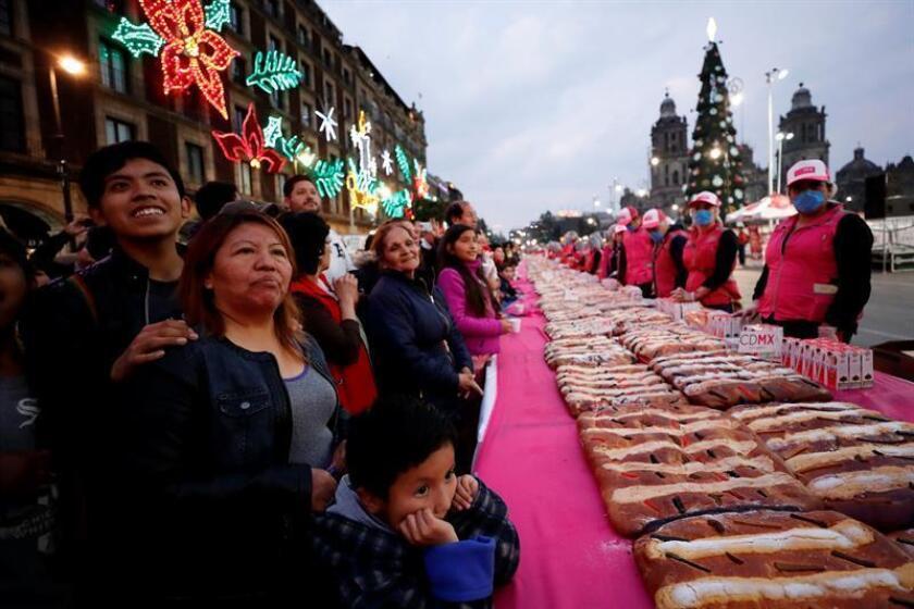 Miles de personas reciben hoy, viernes 5 de enero de 2018, una porción de la rosca de 1.440 metros y más de 9 toneladas de peso con la que la Ciudad de México (México) celebró el Día de Reyes en el Zócalo capitalino y, que por primera vez, se elaboró una parte destinada a las personas que padecen de diabetes. EFE