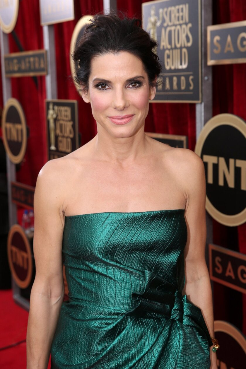 FILE - In this Jan. 18, 2014, file photo, Sandra Bullock arrives at the 20th annual Screen Actors Guild Awards at the Shrine Auditorium, in Los Angeles. Police arrested Joshua Corbett on June 8, 2014, inside Bullock's Los Angeles home and he was later charged with felony stalking. A search of Corbett's home turned up an arsenal of illegal weapons, including machine guns and tracer ammunition. None of the weapons were with Corbett when he broke into Bullock's home and he has pleaded not guilty to all charges. In 2010, Bullock renewed a restraining order against another man who had been stalking her since 2003 and had traveled to Wyoming to try to meet the actress after he was released from a mental hospital in Tennessee. (Photo by Matt Sayles/Invision/AP, File)