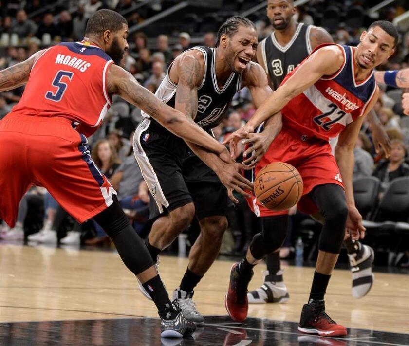 El jugador de los San Antonio Spurs Kawhi Leonard (2i), trata de defender el balón de los jugadores de los Wizards de Washington Otto Porter, Jr. (d) y Markieff Morris, durante el partido de hoy de la NBA. EFE
