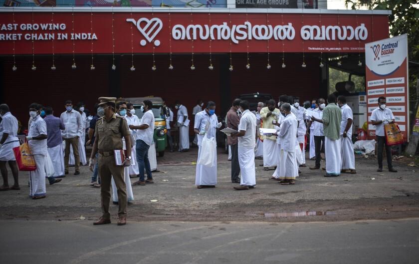 Representantes de candidatos esperan entrar a un centro de votación en Kochi, estado de Kerala