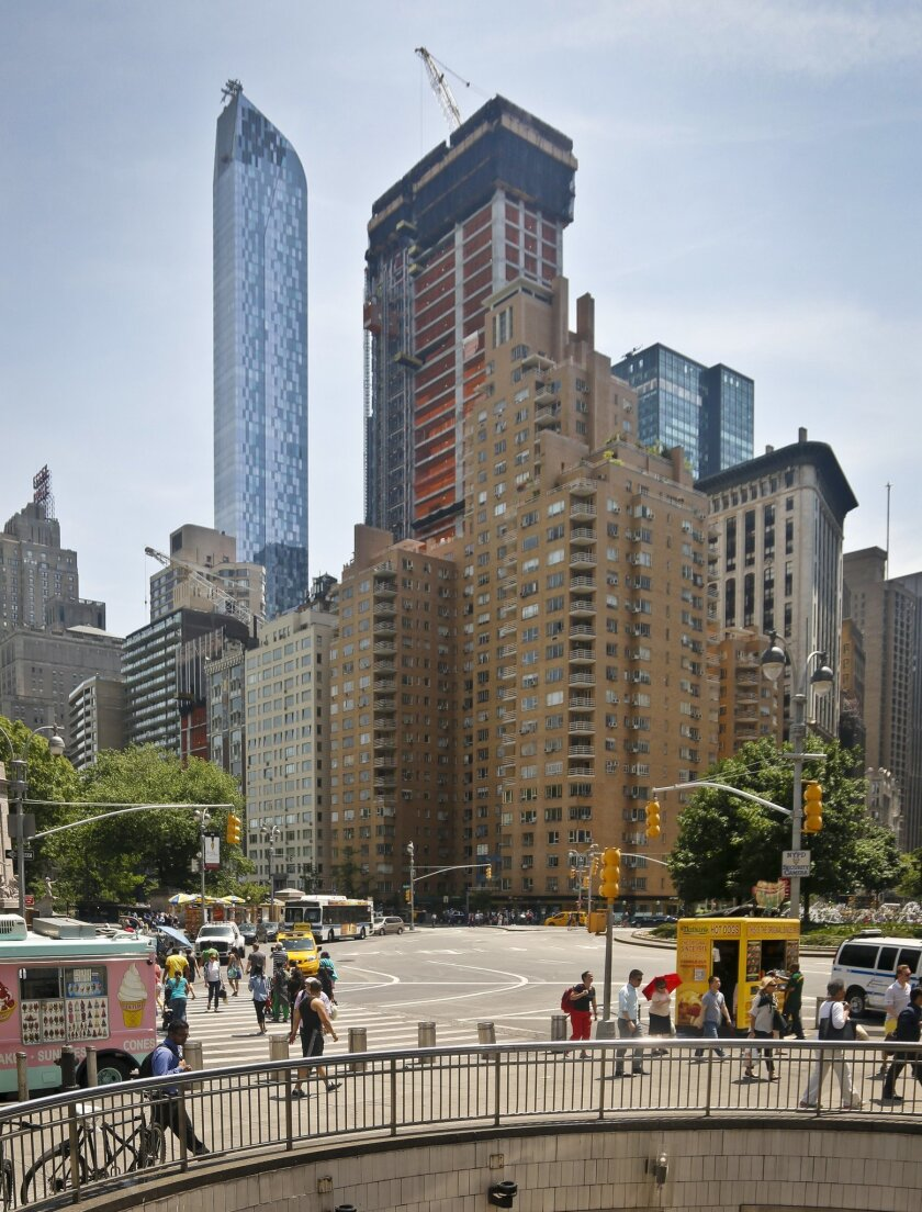 """A luxury 90-floor apartment skyscraper called """"One57,"""" left, rises above all other buildings overlooking Central Park, while a crane sits atop ongoing construction for a new condominium skyscraper at 220 Central Park South, Thursday May 26, 2016, in New York. A penthouse in One57 went for $100.5 mi"""