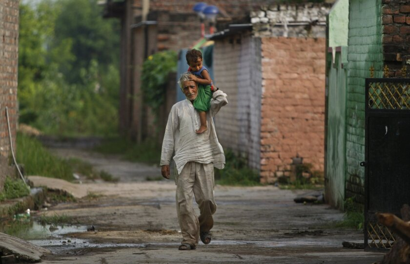 In this Thursday, Aug, 20, 2015, photo, Indian villager Pritam Lal carries his grandson on his shoulder as he walks back to his house, near international border of India and Pakistan in Akhnoor sector, 33 kilometers (21 miles) from Jammu, India. On the face of it these villages in the Jammu region of Indian Kashmir seem idyllic, but over the last two weeks these villages have been witness to an angry exchange of fire and mortar shells between Indian and Pakistani soldiers. This isn't the first time that these villages have borne the brunt of the animosity between India and archrival Pakistan. And this likely won't be the last. (AP Photo/Channi Anand)