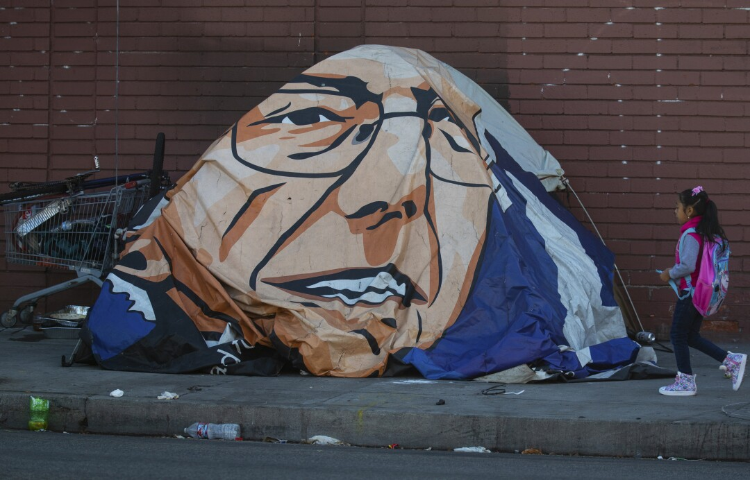A girl walks past Leneace Pope's tent, covered with a likeness of Bernie Sanders.