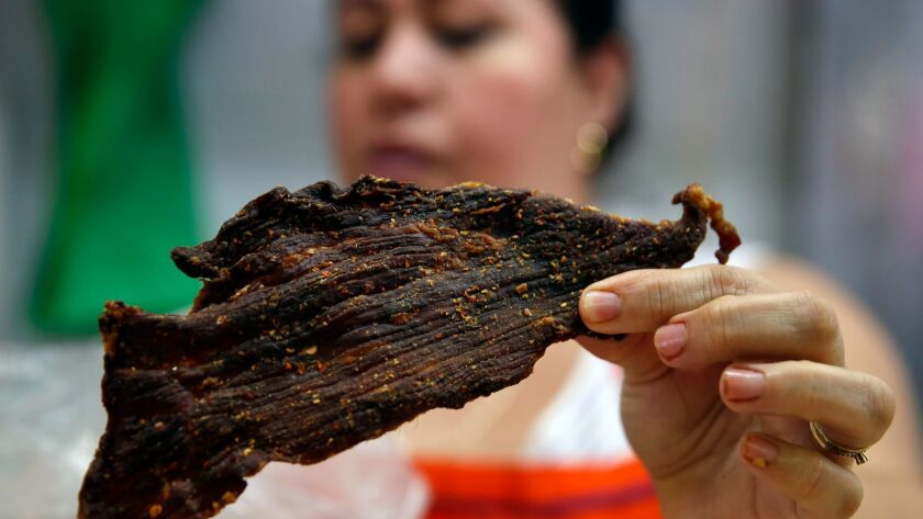 HERMOSILLO, MEX-JUNE 18, 2019: Carla Viega holds a piece of dried beef with chili at the Carniceria