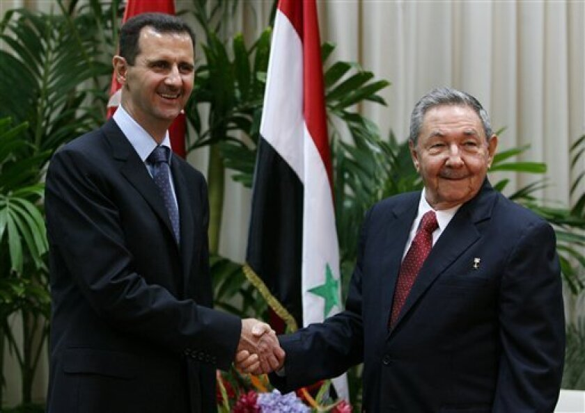 Cuba's President Raul Castro, right, shakes hands with Syria's President Bashar al-Assad at Revolution palace in Havana, Monday June 28, 2010. Al-Assad is in Cuba for an official visit.  (AP Photo/Ismael Francisco, Prensa Latina)