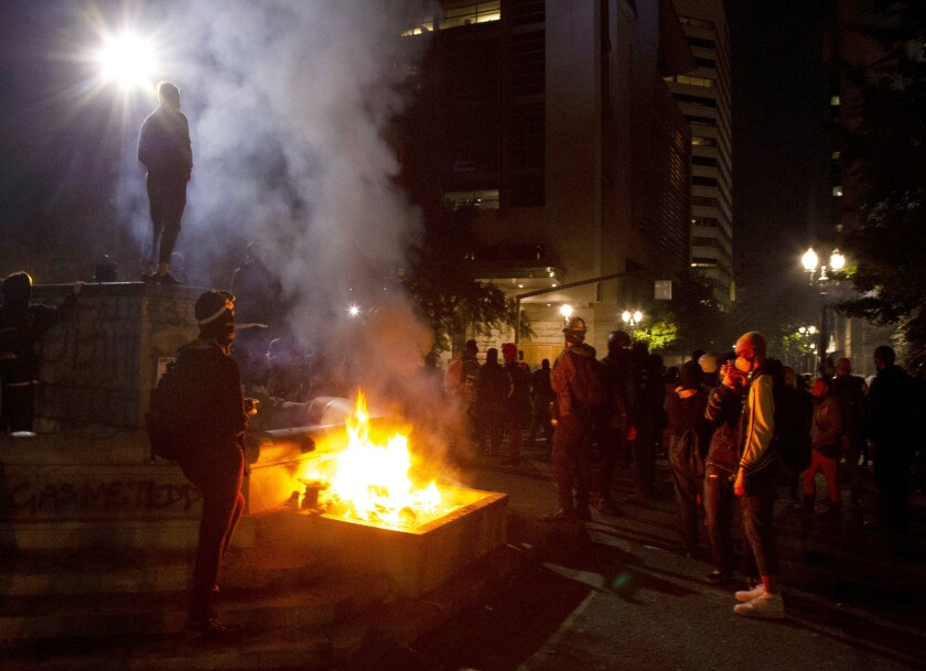 Protesters gather near a fire in downtown Portland, Ore.