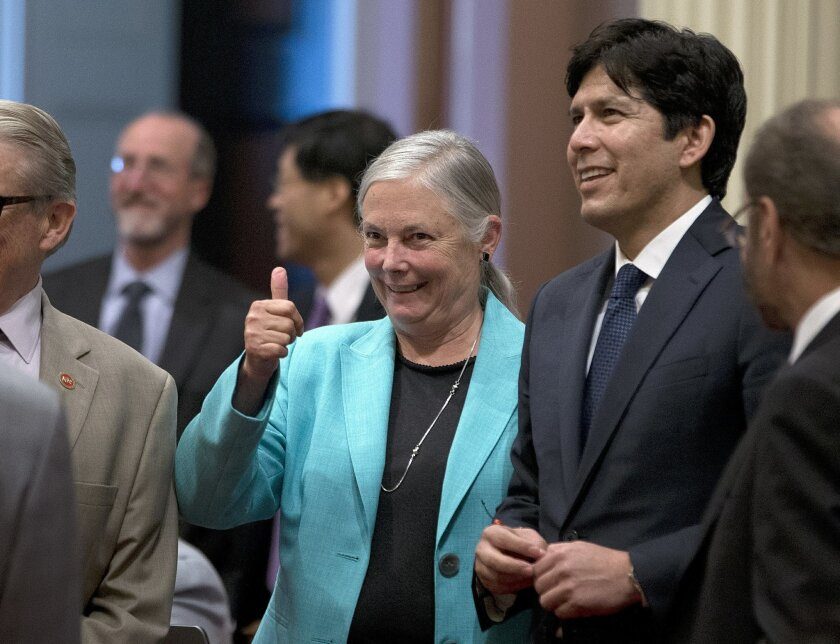 State Sen. Fran Pavley, D-Agoura Hills, flanked by Senate President Pro Tem Kevin de Leon, D-Los Angeles, right, gives a thumbs up after her measure for a 10-year extension of the state's climate change law was approved by the Senate, Wednesday, Aug. 24, 2016, in Sacramento, Calif. SB32 sets a new goal to reduce greenhouse gas emissions to 40 percent below 1990 levels by 2030. The bill now goes to the governor. (AP Photo/Rich Pedroncelli)