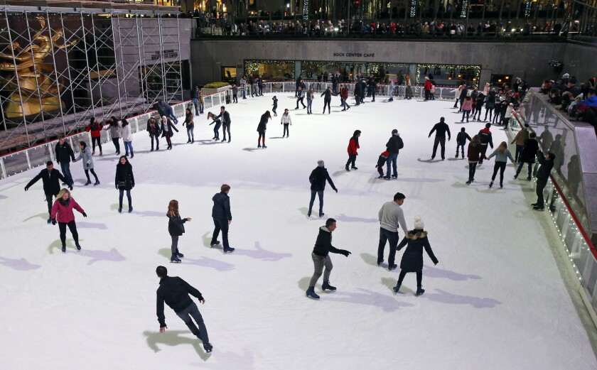 FILE- This Nov. 12, 2017 file photo shows skaters at the Rockefeller Center skating rink in New York. The sunken rink located in midtown Manhattan is set to open to skaters on Saturday, Nov. 21, 2020. The rink is operating at a reduced capacity, with skate time limited to 50 minutes. Masks are required as a futher pandemic safety measure. (AP Photo/Kathy Willens)