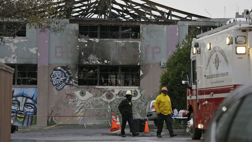FILE - In this Dec. 7, 2016 file photo, Oakland fire officials walk past the remains of the Ghost Sh