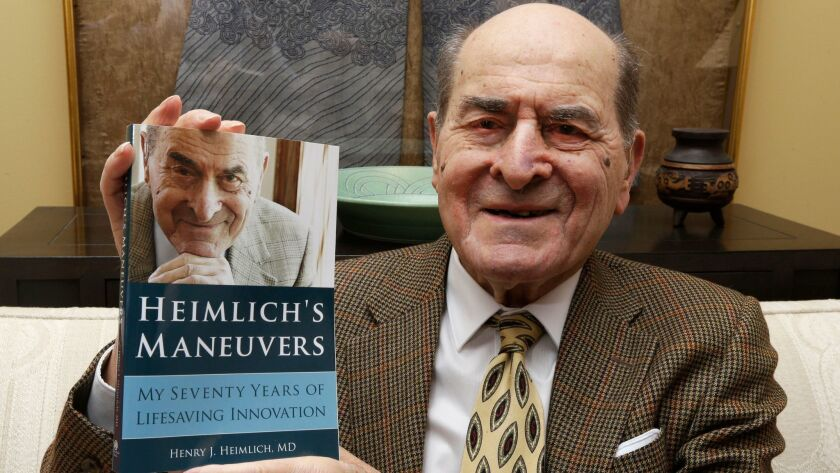 In this Feb. 5, 2014, file photo, Dr. Henry Heimlich holds his memoir prior to being interviewed at his home in Cincinnati.