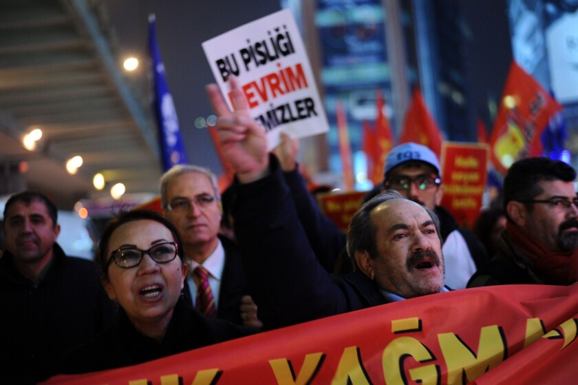 """A Turkish protester holds up a placard reading """"Only revolution can clear this corruption"""" as others chant slogans during a demonstration in Istanbul on Dec. 30 against the government of Prime Minister Recep Tayyip Erdogan."""