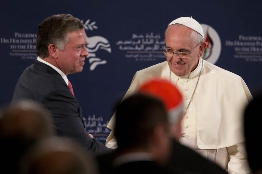 King Abdullah II of Jordan greets Pope Francis in Amman's Al Husseini Royal Palace.