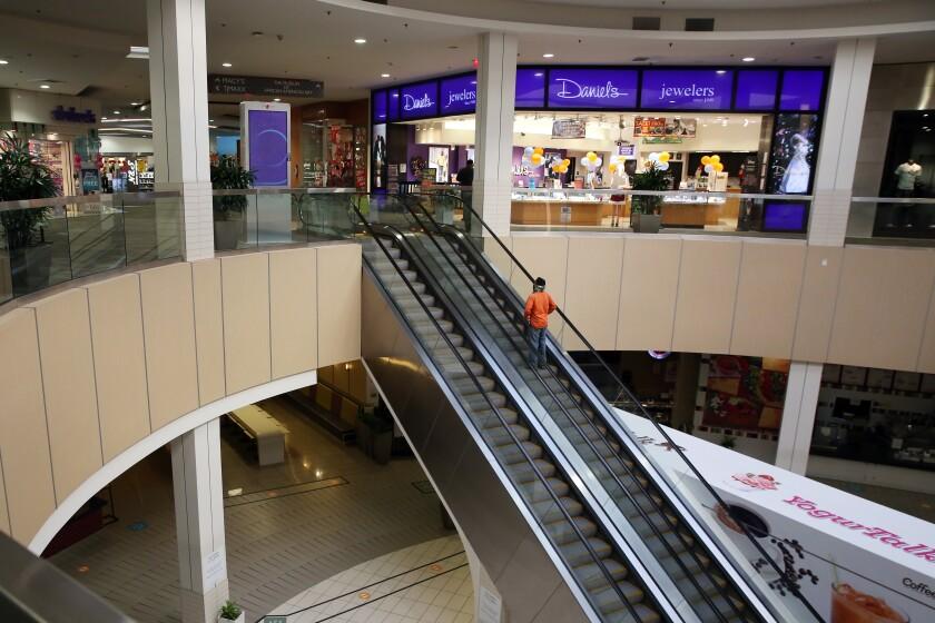 A person rides an escalator at a mall.