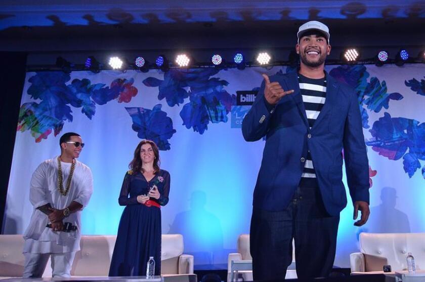 El reguetonero puertorriqueño Don Omar (d) saluda a los asistentes durante su participación en la Conferencia Billboard de la Música Latina con Daddy Yankee (i) y la directora de contenido latino de la revista Billboard, Leila Cobo (c), el miércoles 27 de abril 2016, en Miami Beach, Florida. EFE/Archivo
