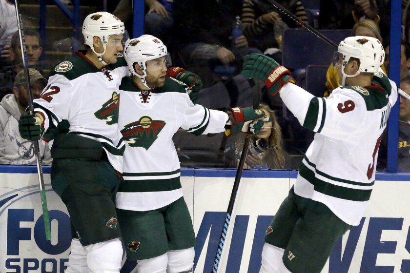Minnesota Wild's Jason Zucker, center, is congratulated by teammates Nino Niederreiter, of Switzerland, and Mikko Koivu, right, of Finland, during the first period of an NHL hockey game against the St. Louis Blues, Saturday, Oct. 31, 2015, in St. Louis. (AP Photo/Jeff Roberson)