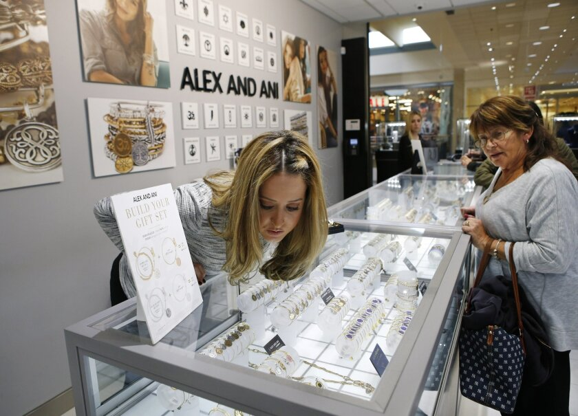 FILE - In this Wednesday, Nov. 18, 2015, file photo, Alana Fusco, left, an employee at Gerald Peters, at the Staten Island Mall in New York, helps a customer choose a bracelet for her niece. On Tuesday, Jan. 26, 2016, the Conference Board releases the Consumer Confidence Index for January. (AP Photo/Kathy Willens, File)