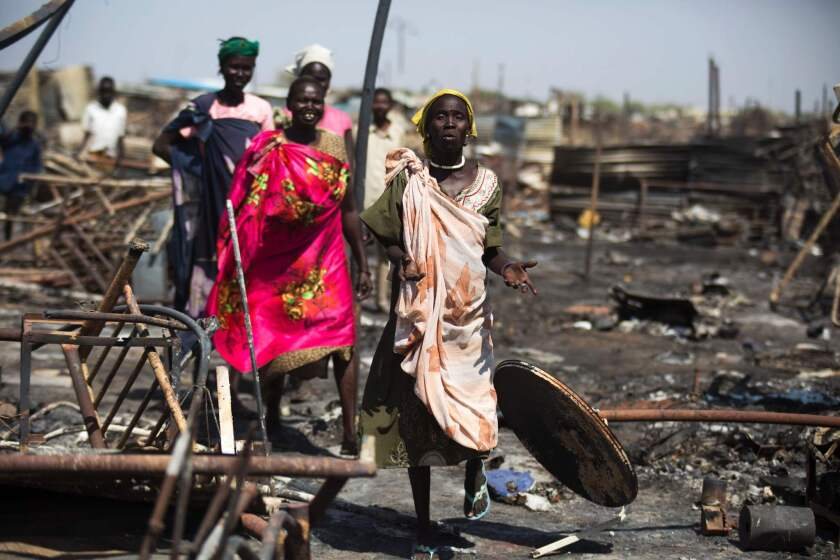 Displaced women residing in the United Nations Protection of Civilians site in Malakal, South Sudan, examine a burnt and looted area, searching for their belongings on Feb. 26.