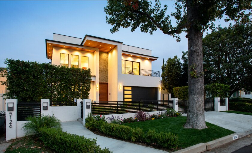 The stylish six-bedroom home expands to three upper-level terraces and a backyard with a fountain-fed pool and spa.