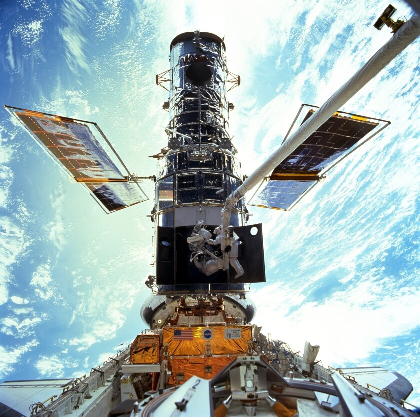 ARCHIVO - En esta imagen provista por NASA/JSC, los astronautas Steven L. Smith y John M. Grunsfeld realizab una actividad extravehicular de mantenimiento del Telescopio Espacial Hubble en diciembre de 1999. El telescopio ha sufrido un desperfecto en su computadora y el trabajo de observación astronómica está detenido, informó la NASA el miércoles 16 de junio de 2021. (NASA/JSC via AP, File)