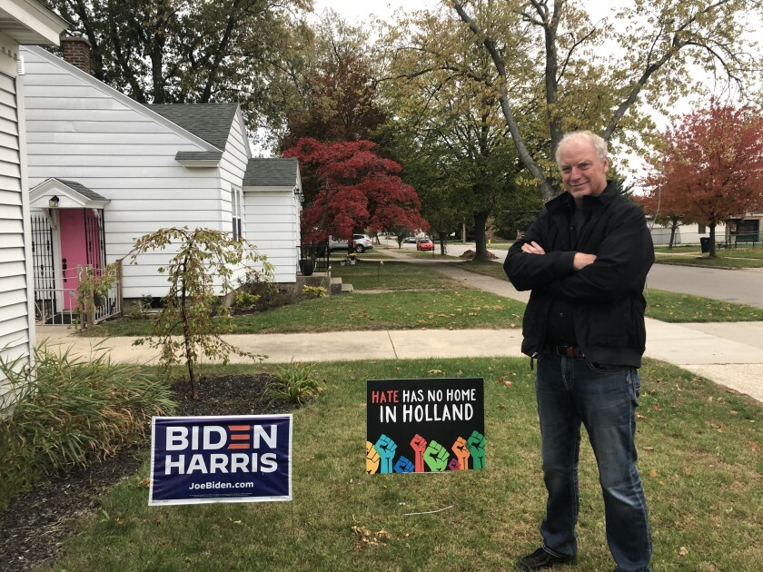The Rev. Keith Mannes stands next to a Biden-Harris sign in the frontyard of his Holland, Mich., home.