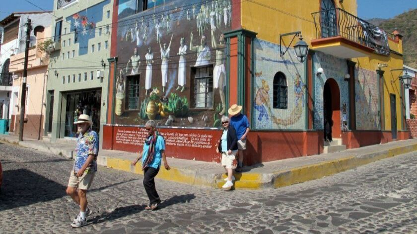 Foreigners walk by a huge mural in Ajijic, Mexico, a retirement haven for Americans and Canadians, in 2011. Mexico is one of several countries that get high marks for health care on expat websites.