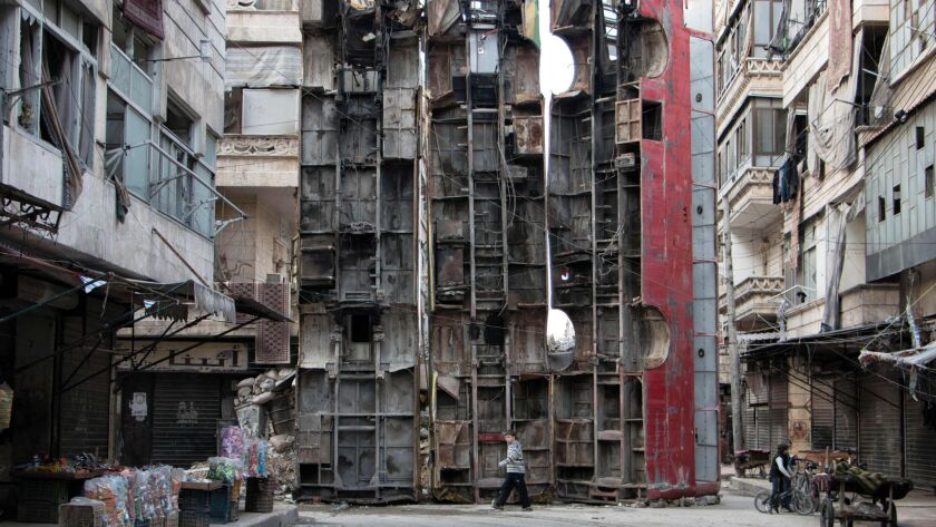 A March 14, 2015, photo shows a young boy walking past a makeshift barricade made of the wreckages of buses to obstruct the view of snipers in the northern Syrian city of Aleppo.