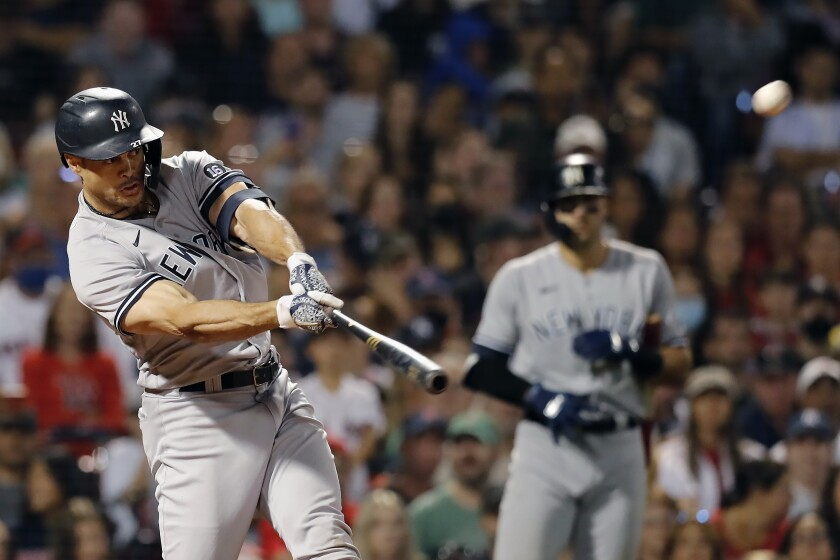 New York Yankees' Giancarlo Stanton hits a grand slam during the eighth inning of a baseball game against the Boston Red Sox, Saturday, Sept. 25, 2021, in Boston. (AP Photo/Michael Dwyer)