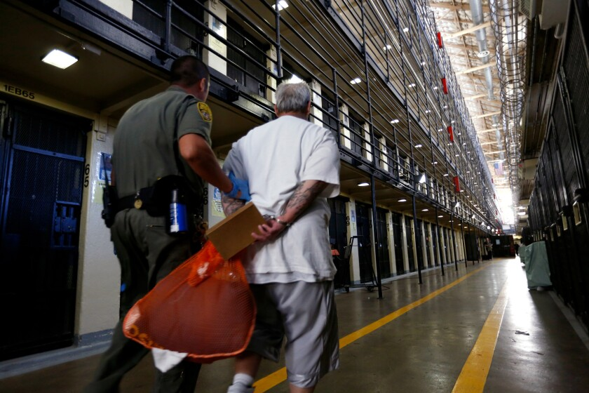 A prison guard holds the arm of a handcuffed inmate carrying an orange bag through the cellblocks at San Quentin State Prison