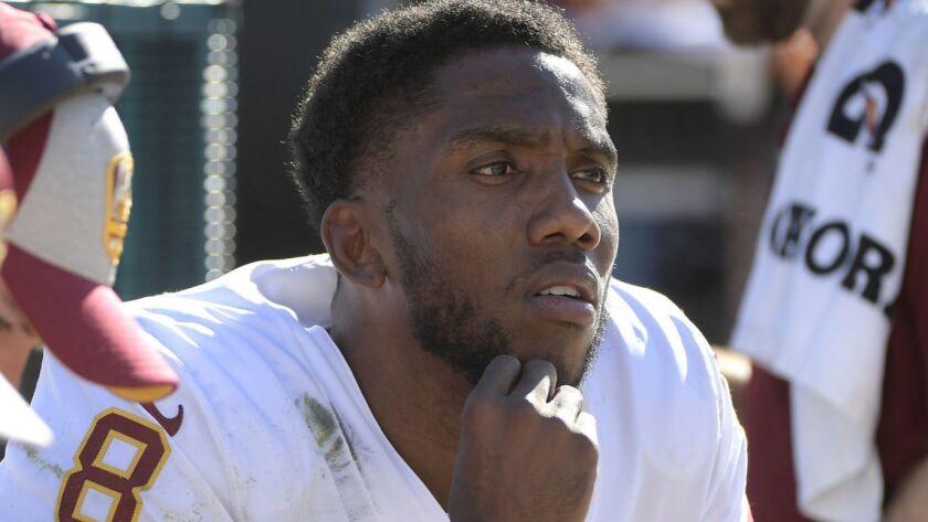 Washington Redskins quarterback Josh Johnson (8) watches play as he takes a break on the bench durin