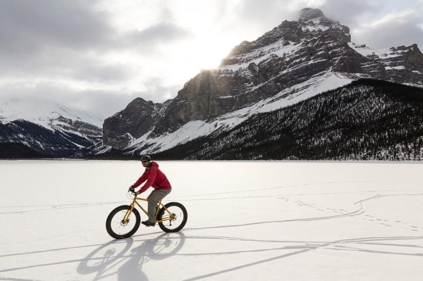 A man circles around a frozen lake on his fat-tire bike