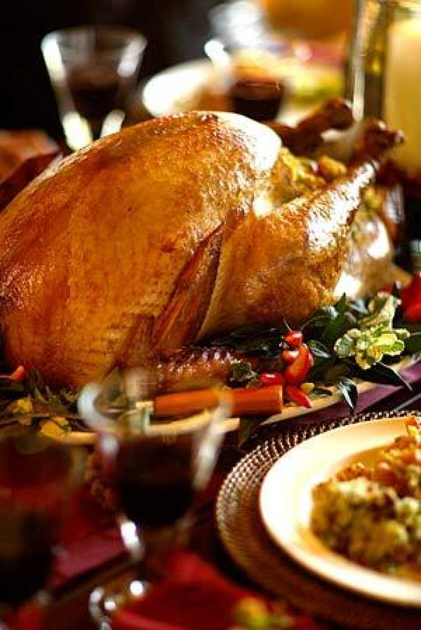 A MEAL TO LINGER OVER: Soy-brined turkey is the centerpiece of a Thanksgiving dinner, served alongside sausage-cornbread stuffing.