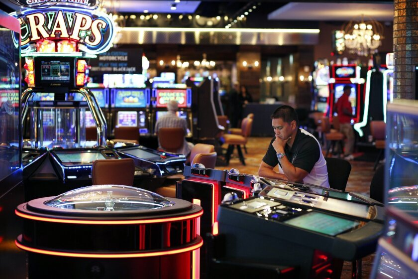 In this Sept. 24, 2015, photo, a man plays an electronic roulette game at the Downtown Grand hotel and casino in Las Vegas. As gamblers move away from traditional slot machines, game-makers and casinos are looking at new ways to keep people playing. (AP Photo/John Locher)