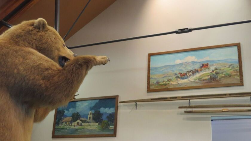 Two Marjorie Reed paintings hang high on a wall at the Valley Center History Museum. A stuffed grizzly has a great, permanent view.