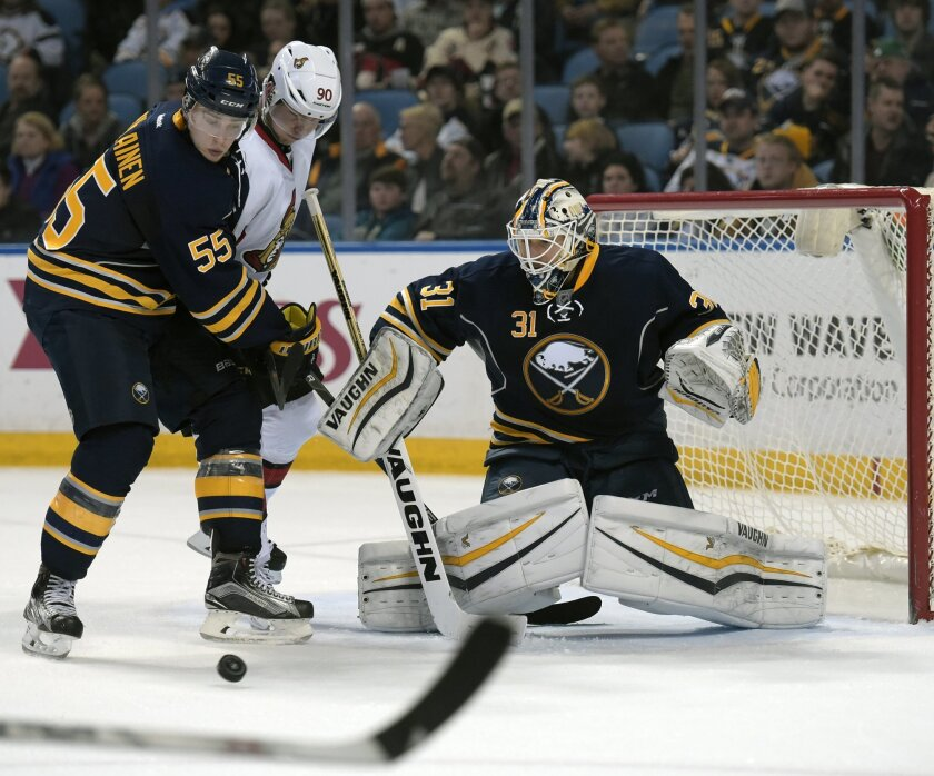 Buffalo Sabres defenseman Rasmus Ristolainen (55) tangles with Ottawa Senators right winger Alex Chiasson (90) as Sabres goaltender Chad Johnson (31) makes a save during the second period of an NHL hockey game, Friday, March 18, 2016, in Buffalo, N.Y. (AP Photo/Gary Wiepert)