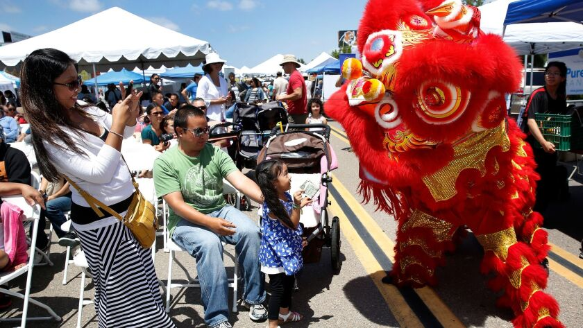 Members of the Southern Sea Lion Dance Troupe engage audience members as they dance the Lion Dance during the Asian Cultural Festival of San Diego.