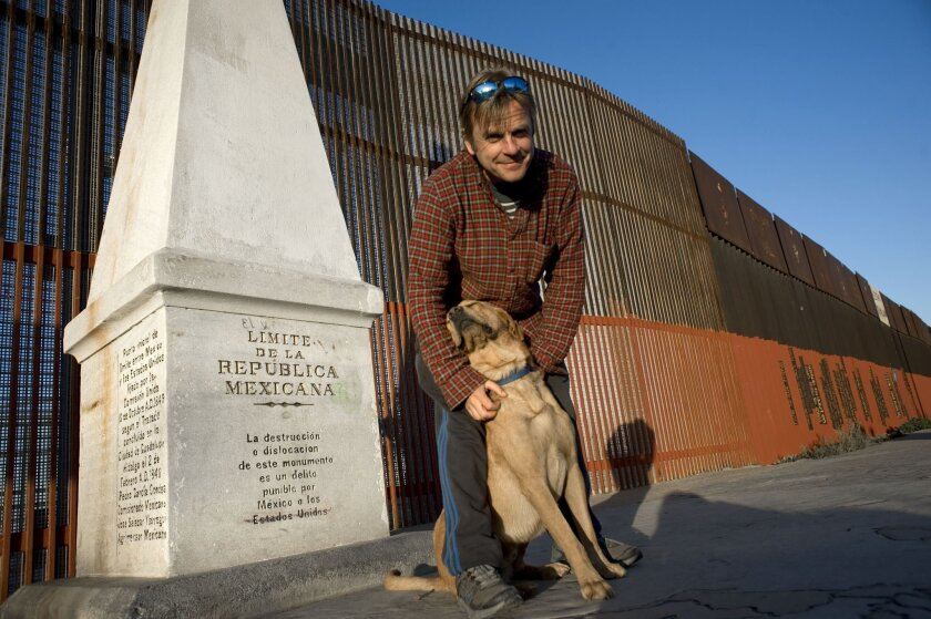 Tom Fremantle and dog Pancho pose by the border fence at Playas de Tijuana Thursday after completing their 1,000-mile journey from El Paso.