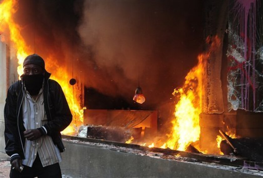 A demonstrator is seen next to a Starbucks burning and stormed by demonstrators during clashes with the police at the general strike in Barcelona, Thursday, March 29, 2012. Spanish unions angry over economic reforms are waging a general strike, challenging a conservative government not yet 100 days