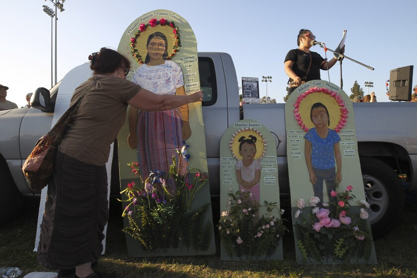 San Diego artist Antonia Davis moves a piece of her artwork that she said represented migrant children killed by U.S. policy as another woman speaks to the crowd during a protest rally demanding the closure of migrant detention camps Friday in San Ysidro.