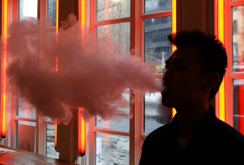 FILE - In this Feb. 20, 2014, File photo, a patron exhales vapor from an e-cigarette at the Henley Vaporium in New York. The first peek at a major study of how Americans smoke suggests many use combinations of products, and often e-cigarettes are part of the mix. It's a preliminary finding, but it highlights some key questions as health officials assess electronic cigarettes. (AP Photo/Frank Franklin II, File)