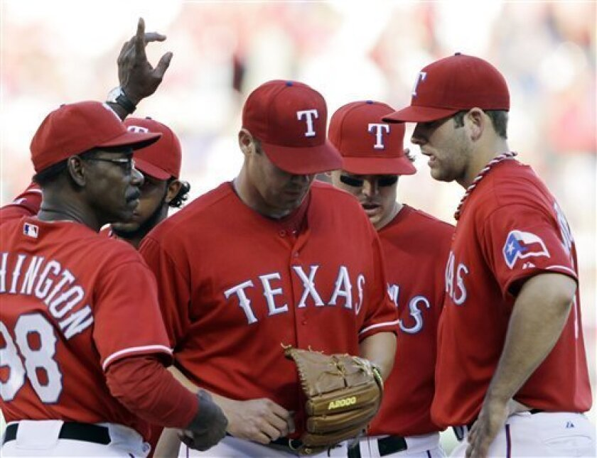 Texas Rangers starting pitcher Colby Lewis, center, is relieved by manager Ron Washington, left, in the sixth inning against the Tampa Bay Rays at Game 3 of baseball's American League Division Series Saturday, Oct. 9, 2010, in Arlington, Texas. Other Texas players are Elvis Andrus, obscured at rear left, Ian Kinsler, rear right, and Mitch Moreland, right. (AP Photo/David J. Phillip)