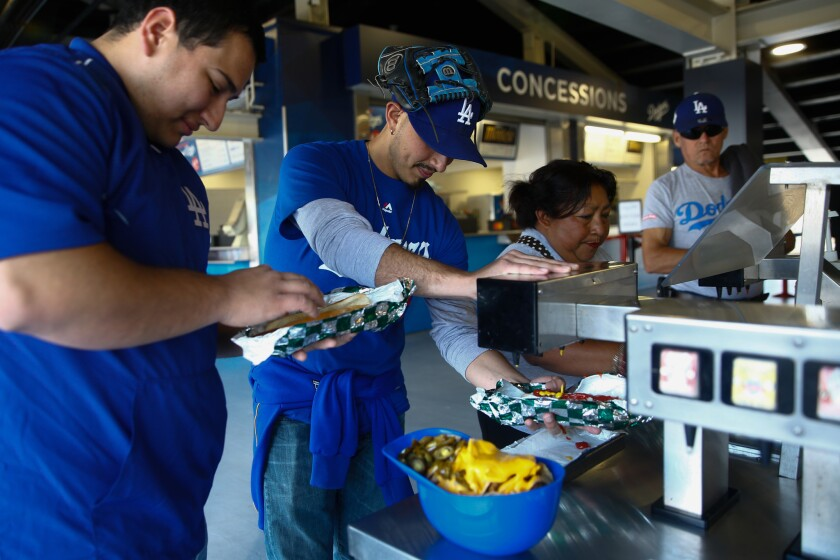 Eric and Steve Soto put condiments on their Dodger Dogs during a game lasr May 27 at Dodger Stadium.