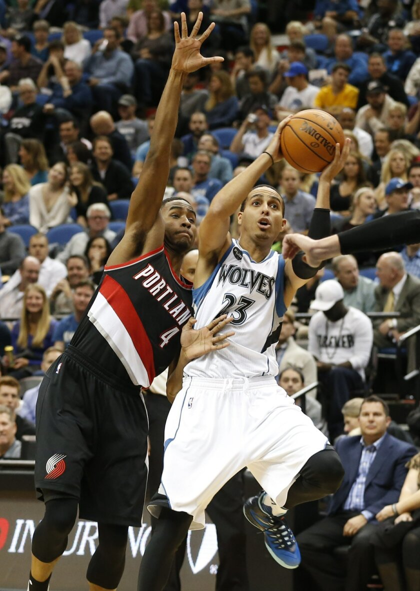 Minnesota Timberwolves' Kevin Martin, right, eyes the basket as Portland Trail Blazers' Maurice Harkless defends in the first half of an NBA basketball game, Monday, Nov. 2, 2015, in Minneapolis. (AP Photo/Jim Mone)