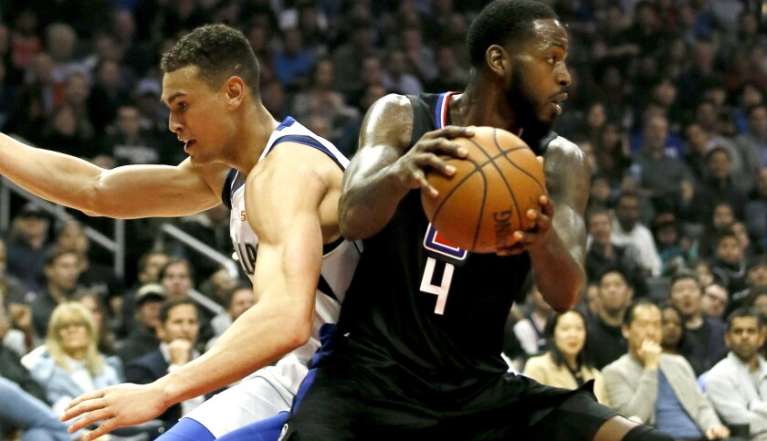 Clippers forward JaMychal Green (4) steals the ball from Mavericks forward Dwight Powell during the first half Monday.