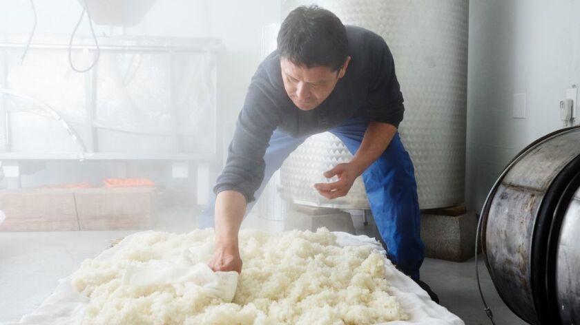 Yoshihiro Sako cools off steamed rice to brew sake at Den Sake Brewery.