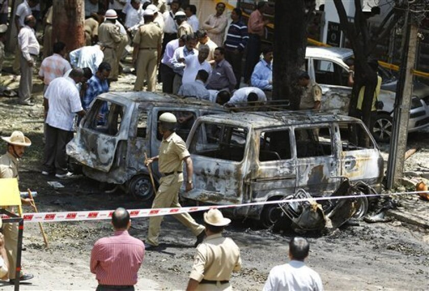 Policemen and officials inspect the site of an explosion at a residential neighborhood near the office of India's main opposition Bharatiya Janata Party in Bangalore, India, Wednesday, April 17, 2013. A powerful bomb exploded Wednesday near the office of the political party, injuring at least 16 pe